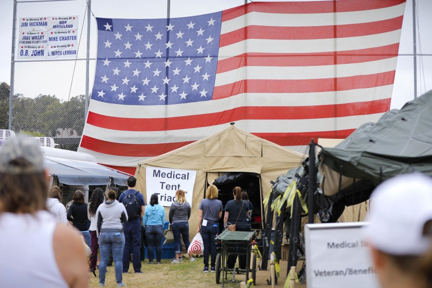 Group Of People In San Diego County Standing In Front Of A Medical Tent With A Large American Flag In Background