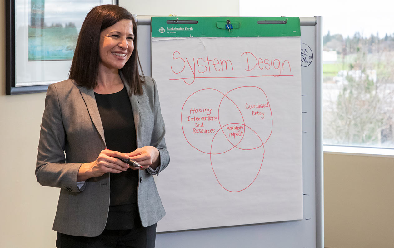 an image of a young woman giving a presentation on a whiteboard at the head of a classroom.